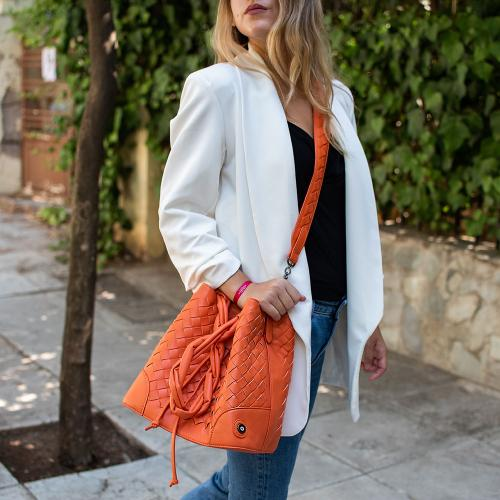 Τσάντα ώμου πλεκτή πουγκί, πορτοκαλί οικολογικό δέρμα με αποσπώμενο λουρί και μάτι από σμάλτο. Διαστάσεις 25x25εκ.