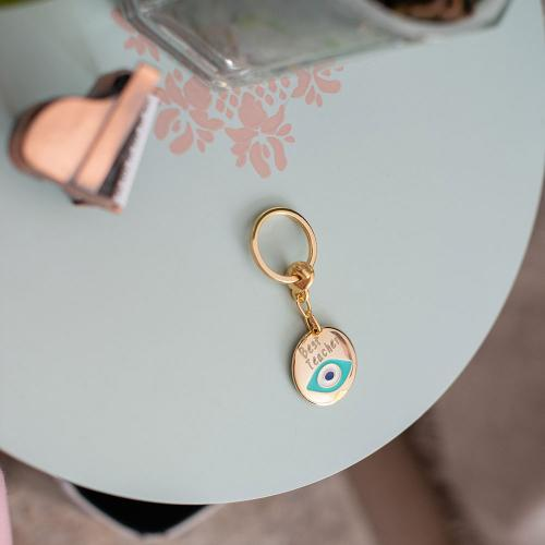 Yellow gold plated alloy key ring ''Best Teacher'', white and turquoise enamel with evil eye.